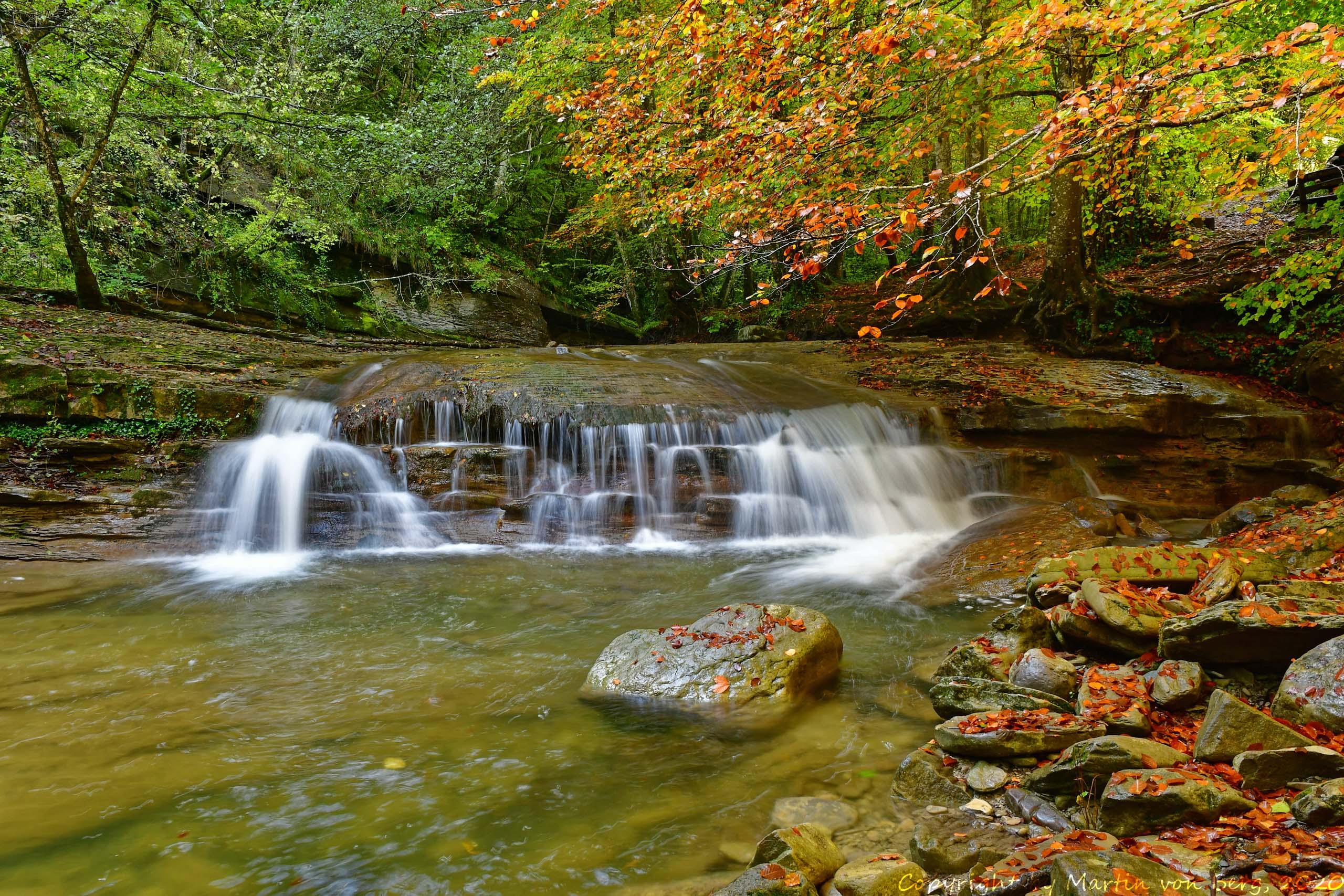 Langzeitaufnahme Wasserfall unter Herbstlaub